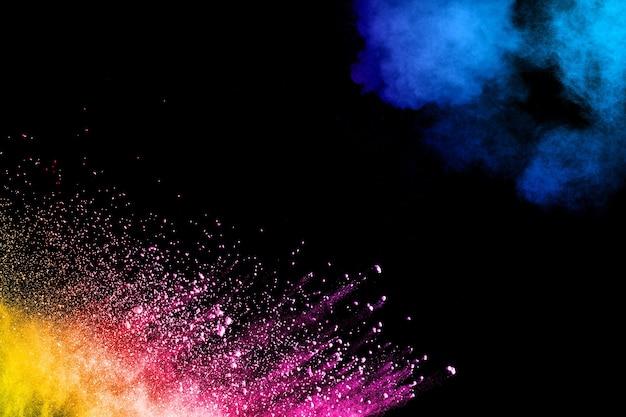 Abstracte kleurrijke poeder explosie op zwarte achtergrond. bevriezen beweging van stof splash. geschilderde holi.
