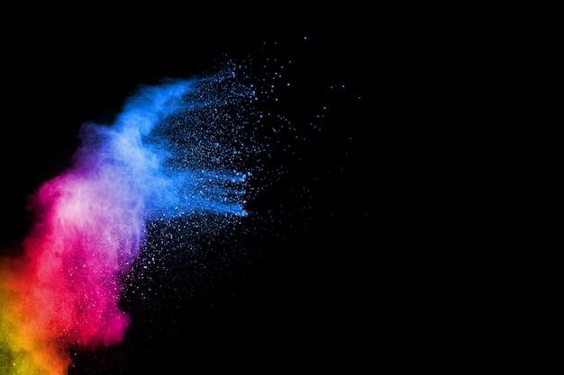 Abstracte kleurrijke poederexplosie op zwarte achtergrond. bevriezen beweging van stofspatten. geschilderde holi.