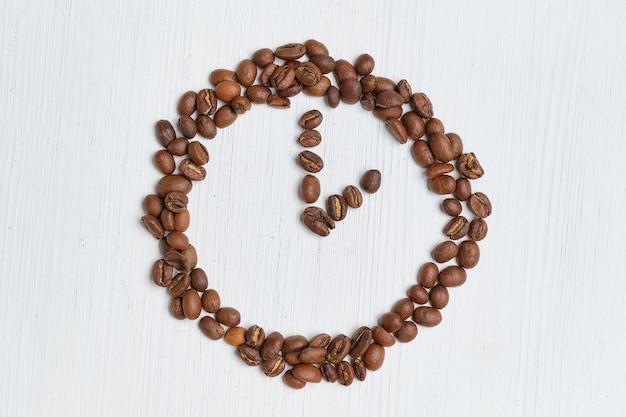 Abstracte klok van koffiebonen op een witte achtergrond.