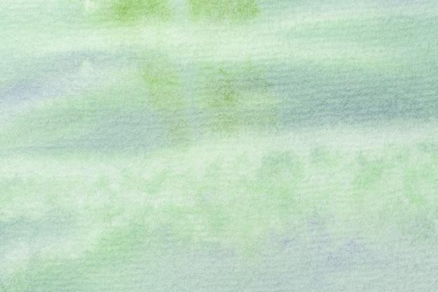 Abstracte kunst lichtgroene en blauwe kleuren als achtergrond. aquarel op doek met zacht olijfgroen verloop.