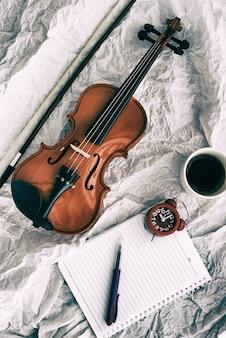 Abstracte kunst ontwerp achtergrond van viool gezet naast rode wekker en boek, op grunge oppervlak