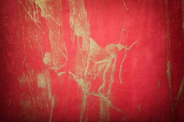 Abstracte kunst rode en gouden achtergrondkleuren met donkere vignet. aquarel op canvas met zacht wijnverloop. fragment van kunstwerk op papier met golvenpatroon. textuur ruby achtergrond.
