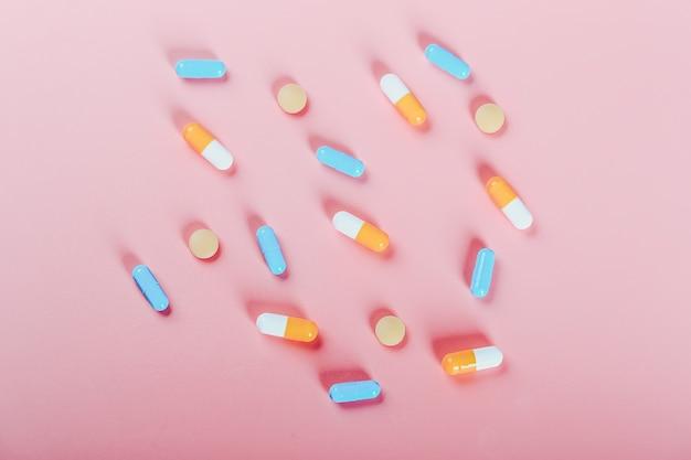 Abstracte medische achtergrond veelkleurige pillen op een roze achtergrond womens gezondheid concept