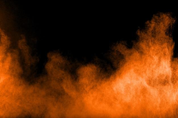 Abstracte oranje poederexplosie op zwarte achtergrond.