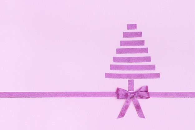 Abstracte paarse kerstboom van decoratief glanzend lint met strik op roze