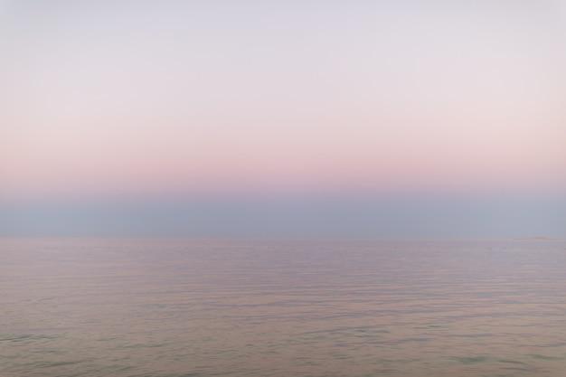 Abstracte pastel roze oceaan zonsondergang vreedzaam water en lucht