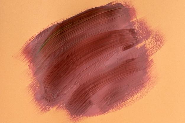 Abstracte penseelstreek op oranje achtergrond