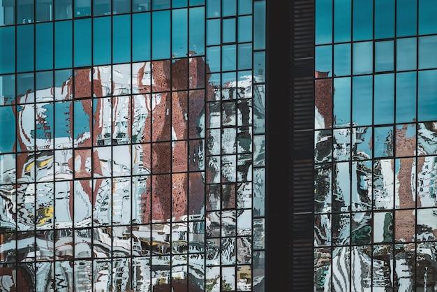 Abstracte reflecties op de glazen gevel van een kantoorgebouw