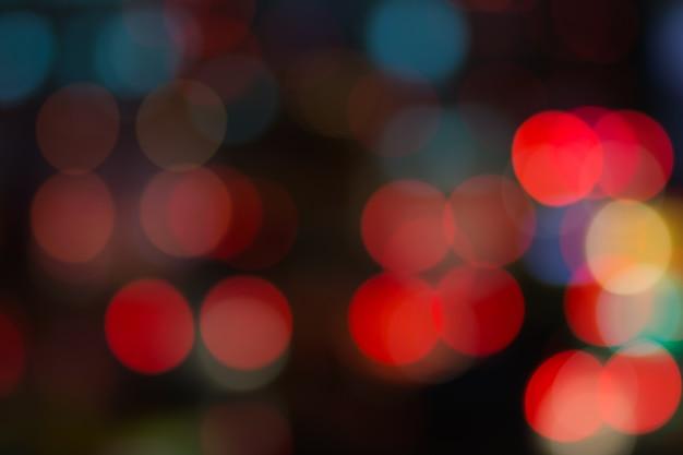 Abstracte rode bokehlichten op wegstraat op de lichte achtergrond van de stadsnacht