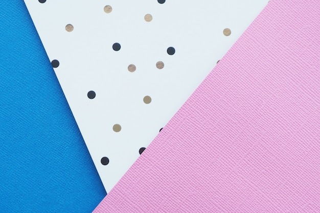 Abstracte roze, blauwe en witboekachtergrond met zwarte en bruine stippen.