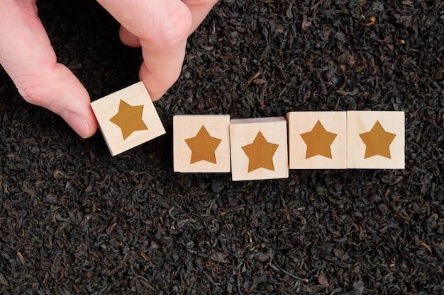 Abstracte score, een waardering van houten sterblokjes houdt een hand tegen de achtergrond van zwarte thee.