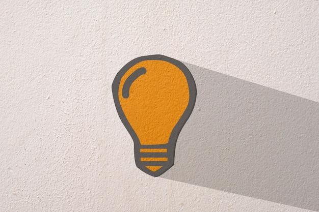 Abstracte sinaasappel denkende gloeilamp op concrete muurachtergrond