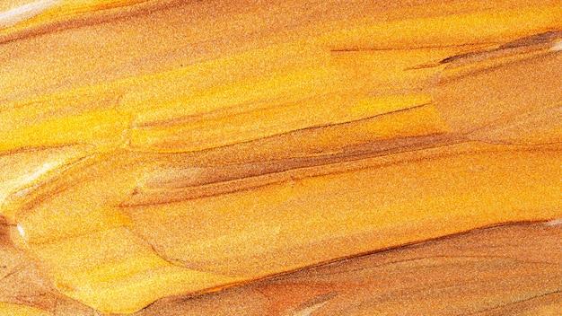 Abstracte sprankelende metalen textuur. brons oranje achtergrond met glinsterende uitstrijkjes. creatieve penseelstreken van gouden sprankelende verf. feestelijke achtergrond