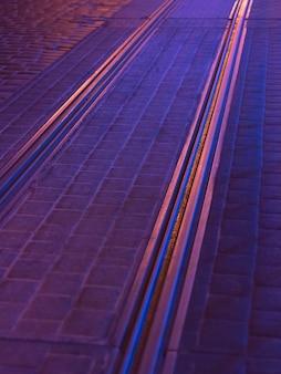 Abstracte stedelijke achtergrond in paars. weg met tramsporen in het licht van de nachtverlichting van de stad