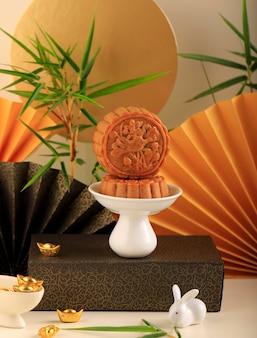 Abstracte stilleven medio herfst festival snack maan cake op crème achtergrond met jonge bamboe boom, geselecteerde focus