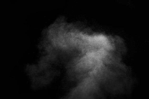 Abstracte stoom met stippen van spray beweegt op een zwarte achtergrond. voor het ontwerp kan gebruik worden gemaakt van becijferde rook.