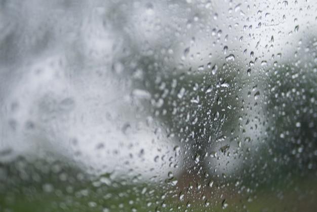 Abstracte textuur onscherpe achtergrond van regendruppel op venster in de selectieve aandacht van het regenseizoen