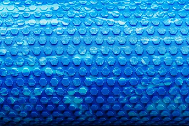 Abstracte textuur van een blauwe massagerol in de vorm van blauwe zeshoekige cellen. het hele scherm als achtergrond.