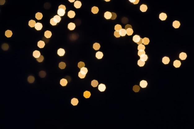 Abstracte verstrooiing van gouden lichten op zwarte achtergrond. vakantieconcept.