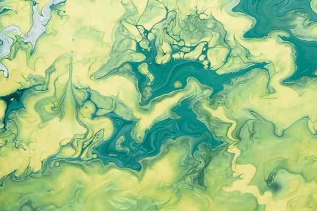 Abstracte vloeiende kunst. vrij vloeiende gele en groene verf. marmeren achtergrond of textuur.