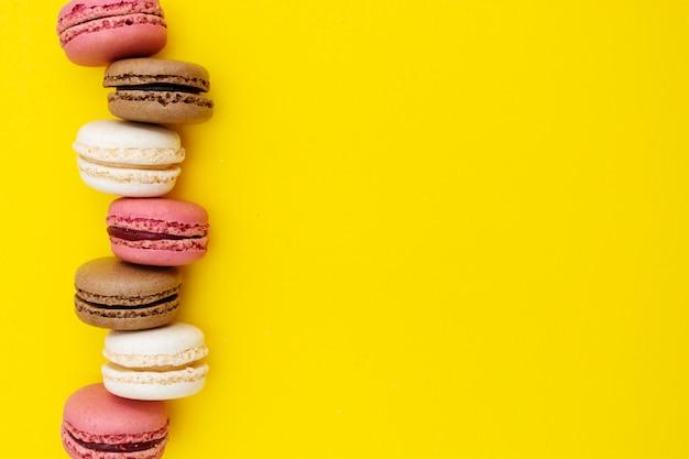 Abstracte voedselachtergrond met makaronscakes op gele achtergrond.