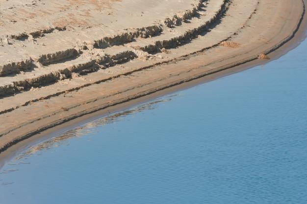 Abstracte vormen aan de oever van een meer met een laag waterpeil