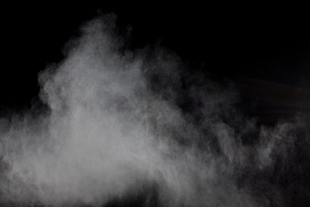 Abstracte witte poederexplosie tegen zwarte achtergrond. het abstracte witte stof ademt uit.