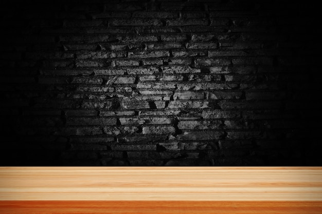 Abstracte zwarte grunge baksteen en houten tafeldek.
