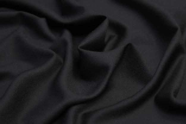 Abstracte zwarte stof doek textuur met vloeibare golf of golvende plooien.