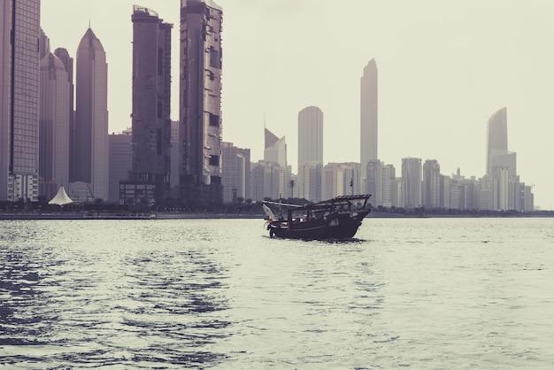 Abu dhabi gebouwen skyline met oude vissersboot aan de voorzijde