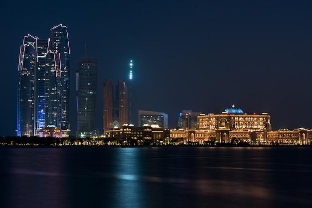 Abu dhabi gebouwen skyline van de zee 's nachts