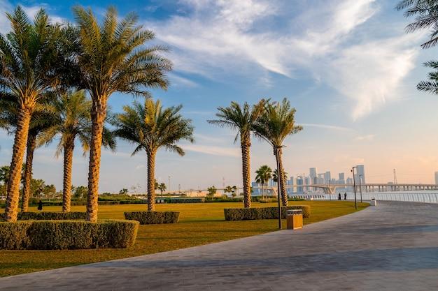 Abu dhabi-parkmening, de v.a.e. magische straten van abu dhabi met hoge glazen gebouwen over de baai.