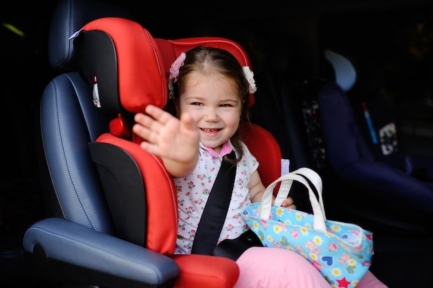 Aby meisje zit in een autokinderzitje