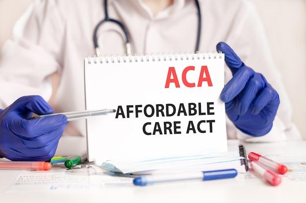 Aca-kaart in handen van arts. de arts dient blauwe handschoenen in met een vel papier met de tekst aca - afkorting van affordable care act, medisch concept.