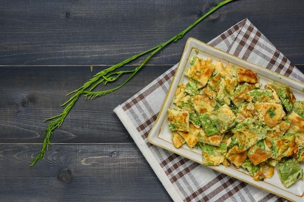 Acacia pennata omelet op een bord met tafelkleed op houten tafel, thais lokaal eten