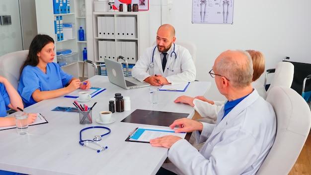Academische bijeenkomst van deskundige artsen die discussiëren over ziektesymptomen die in de vergaderruimte van het ziekenhuis werken. kliniekdeskundige therapeut in gesprek met collega's over behandeling van patiënten