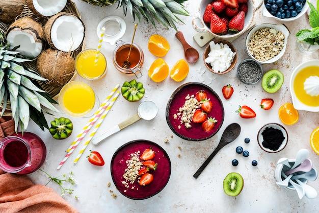 Acai-kom bereiden in platliggende stijl met tropisch fruit en granen