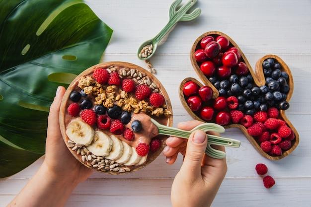 Acai smoothie, muesli, zaden, vers fruit in een houten kom in vrouwelijke handen met cactuslepel. plaat gevuld met bessen