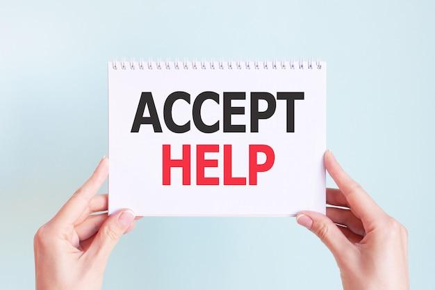 Accepteer help woord inscriptie op wit kaartpapier blad in handen van een vrouw. zwarte en rode letters op wit papier. bedrijfsconcept.
