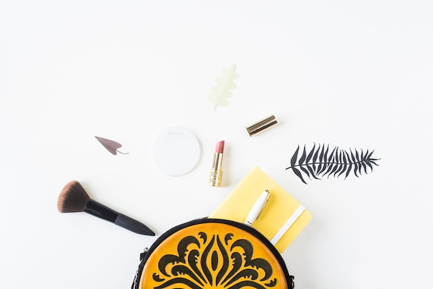 Accessoires en inhoud van een heldere vrouwelijke tas met oranje ornament