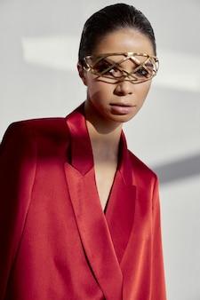 Accessoires op het gezicht van een modieuze vrouw in een rood jasje op een lichte achtergrond