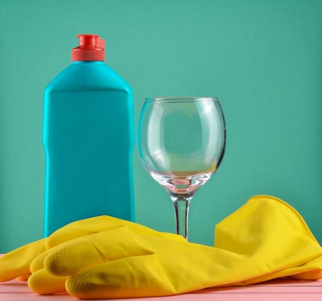 Accessoires voor afwassen en huis schoonmaken. afwassen. fles wasmiddel, glas en gele rubberen handschoenen