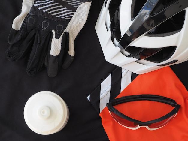Accessoires voor bergfietsen. zwarte herenjersey, bril, handschoenen en witte fietshelm. sportaccessoires, sportuitrusting. bovenaanzicht
