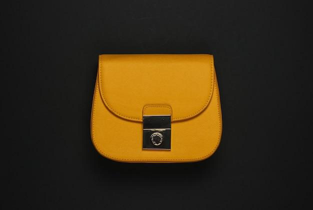 Accessoires voor dames. gele leerzak op een zwarte achtergrond. bovenaanzicht