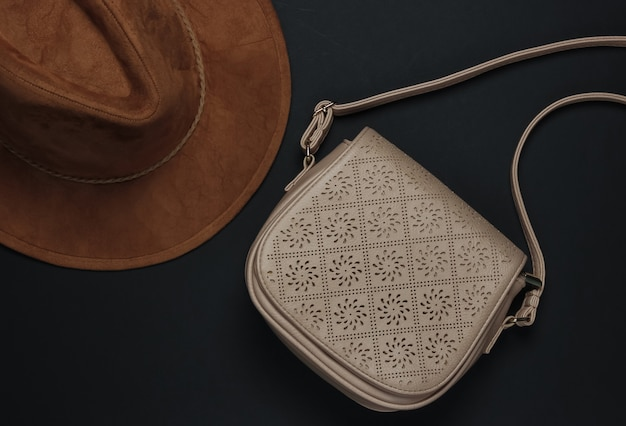 Accessoires voor dames op een zwarte achtergrond. hoed, leren tas. bovenaanzicht