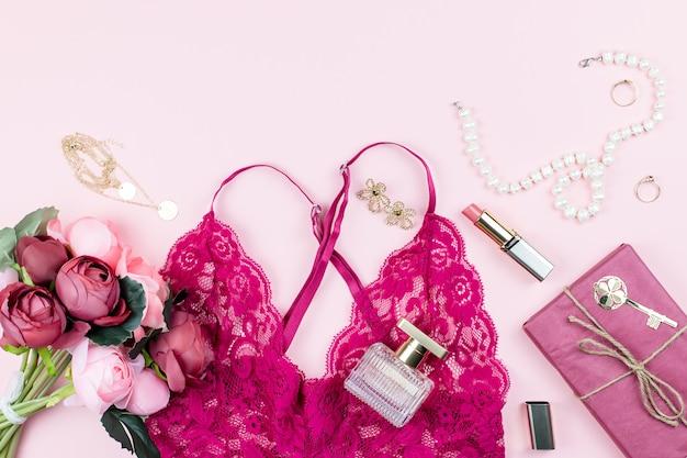 Accessoires voor damesmode, make-up producten en rode lingerie op pastel achtergrond.