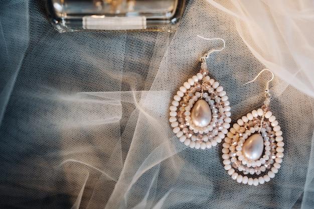 Accessoires voor de bruid. oorbellen aan de sluier. witte bruiloft oorbellen. ruimte voor tekst en advertenties.