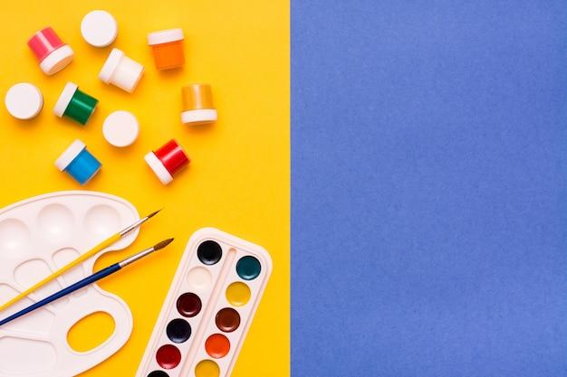 Accessoires voor het tekenen van aquarel, gouache en penselen op een geelblauwe ondergrond