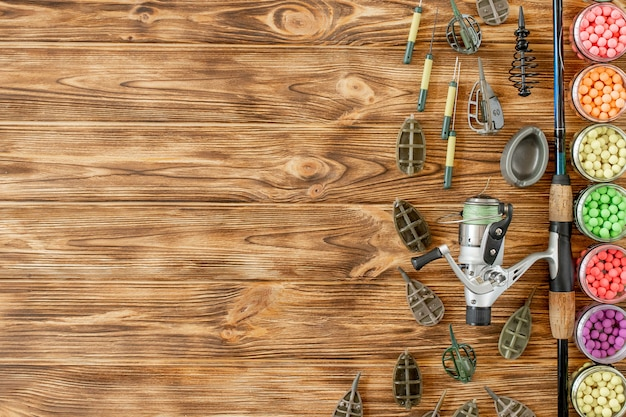 Accessoires voor karpervissen en visaas op houten planken met kopie ruimte