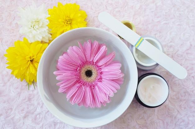 Accessoires voor manicure, een bad voor nagels met een gerbera, een nagelvijl, potten met room, bloemen